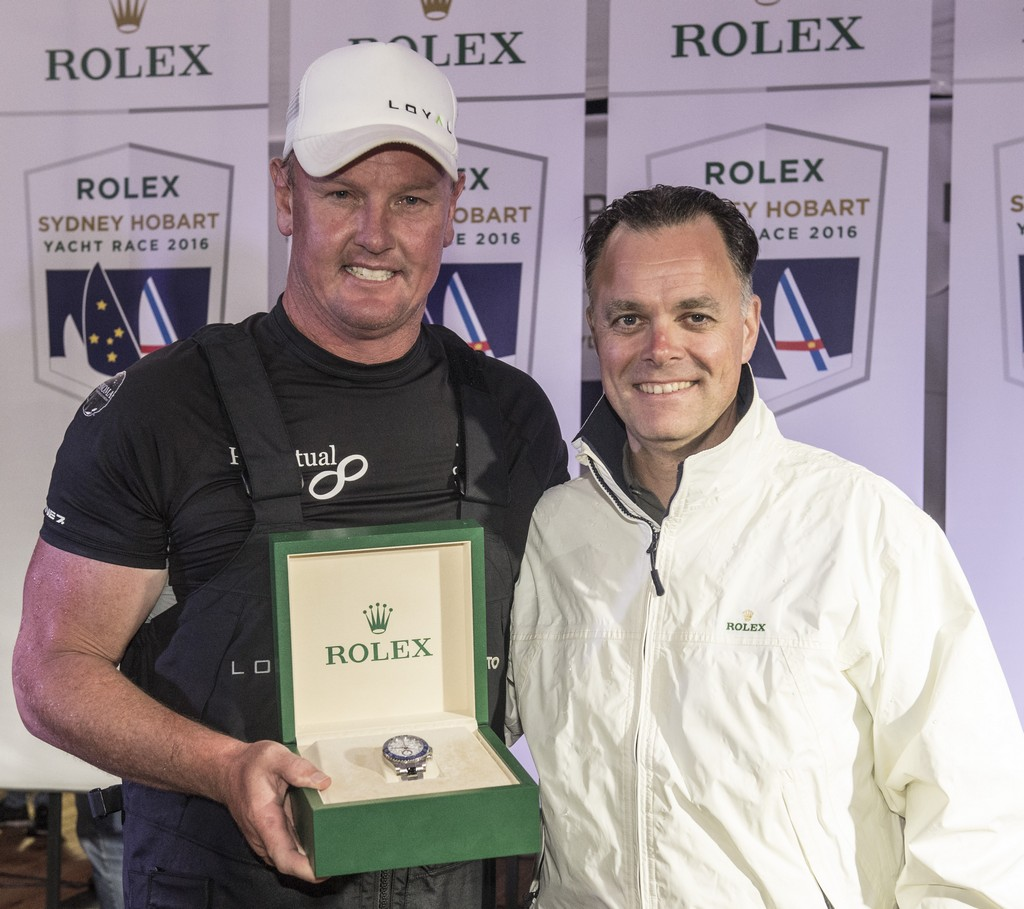 Anthony Bell (left), owner/skipper of line honours winner PERPETUAL LOYAL receives a Rolex Yacht-Master II timepiece from Joël Aeschlimann, Rolex Geneva